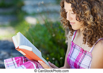 teenage girl with curly hair reading a book outside
