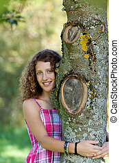 Young Girl Embracing Tree In Park - Portrait of happy young...