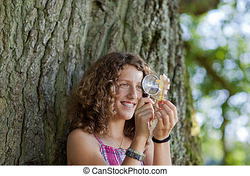 Girl Looking At Leaf Through Magnifying Glass At Park -...