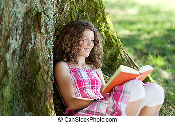 teenage girl reading a book under a tree