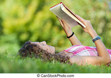 Girl Reading Book While Lying On Grass - Teenage girl...