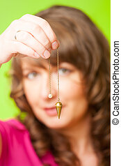 Pendulum - Beautiful woman with pendulum in her hand, tool...