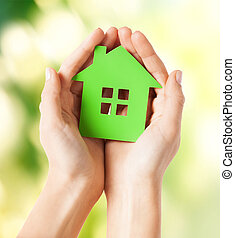 hands holding green house - closeup picture of woman hands...
