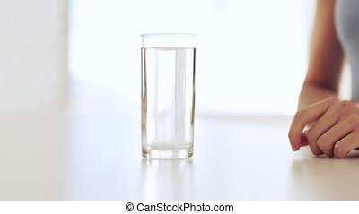 woman dissolving a pill in glass of water - footage of woman...