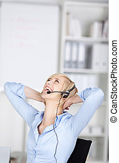happy woman using headset folding hands behind head