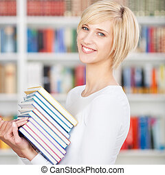 Young Woman Carrying Stacked Books In Library - Portrait of...