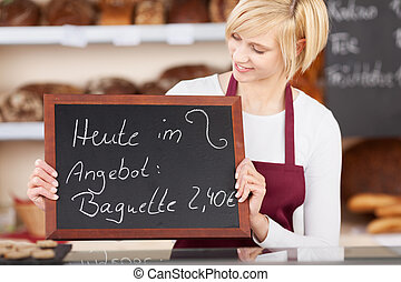 Waitress Holding Slate With Offer Written On It At Bakery -...