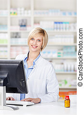 Pharmacist Using Computer At Pharmacy Counter - Portrait of...