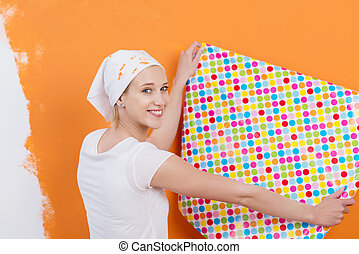 Woman Holding Wallpaper Against Orange Colored Wall -...