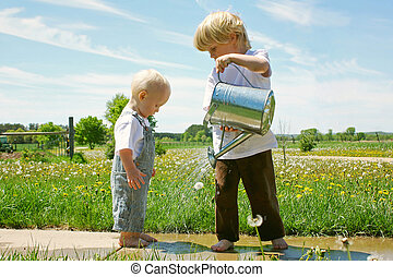Bother Watering Baby - A preschool age blonde boy is...