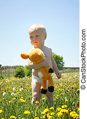 Baby with Stuffed Animal in Field - A cute baby boy stands...