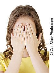 Young teen woman covering her face with hands, isolated on...