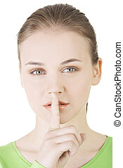 Hush be quiet woman isolated. Teen girl with finger on her lips.