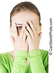 Shy or scared teenage girl peeking through covered face ,...