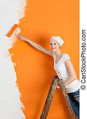 Young Woman Painting Wall With Roller In House - Portrait of...