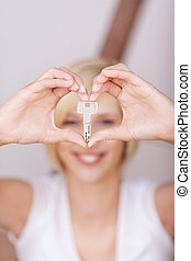 Women's Hands Forming Heart While Holding House Key -...