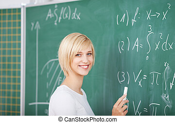 Female Student Solving Sums On Chalkboard In Classroom