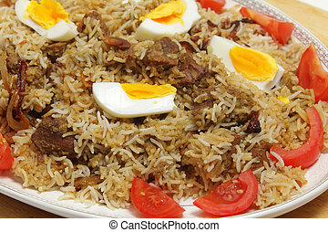 Beef biryani served with tomato and cucumber