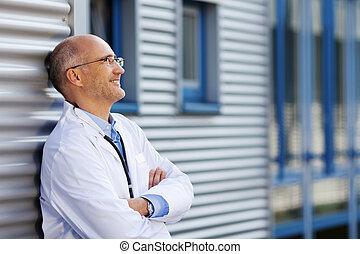 Thoughtful mature doctor with arms crossed smiling while...