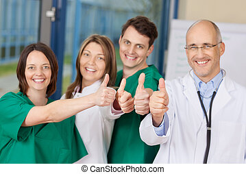 Team Of Doctors Gesturing Thumbs Up Sign - Portrait of...