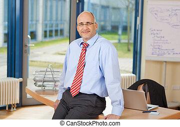 Mature Businessman Sitting On Desk - Portrait of confident...