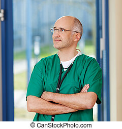 Surgeon With Arms Crossed Looking Away - Thoughtful male...