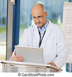 Doctor Using Laptop At Podium - Mature male doctor using...