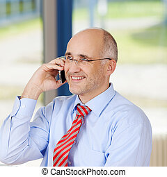 Businessman Using Cell Phone While Looking Away - Mature...