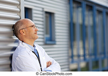 Doctor Leaning On Wall While Looking Away - Thoughtful...
