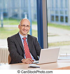 Confident Businessman With Laptop At Desk - Portrait of...