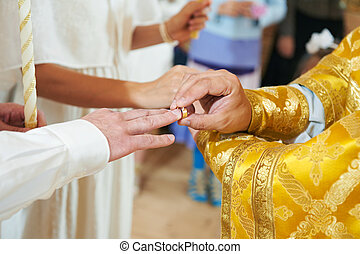 Orthodox wedding ceremony - Bride and groom hands with ring...