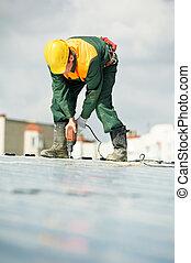 Worker builder roofer at metal profile work