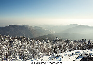 Winter landscape of mountains with snow under blue cloudy sky. Russia, Pidan