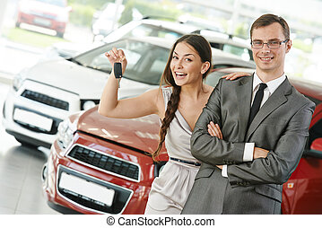 Car selling or auto buying - Happy young couple with keys...