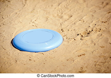 Frisbee lying in sand - A blue Frisbee disc lying on the...