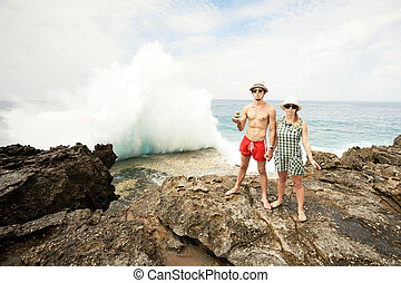 A young man and woman in the seacoast, huge wave crashing on the rocks  in the background. Three round stones in a hands of man.