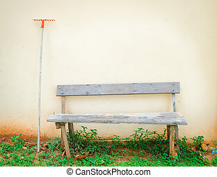 old outdoor wood bench and rake against the wall