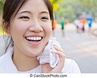 Asian woman wiping sweat with a towel after exercising