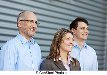 Businesspeople Looking Away Against Shutter - Happy...