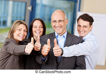 Businesspeople With Thumbs Up Sign In Office - Businessmen...