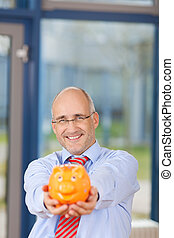 Mature Businessman Holding Piggybank In Office
