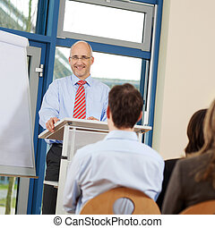 Businessman Giving Presentation To Coworkers - Portrait of...