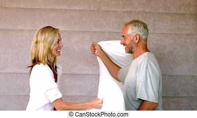 Mature couple pillow fighting at ho