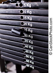 Close up of weights in a gym with the pin at 25kg.