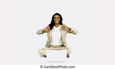 Woman cheering in front of laptop sitting cross legged in...