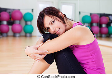 Tired woman resting head on her knees after working out in...