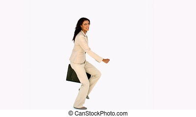 Businesswoman jumping with her suitcase in slow motion