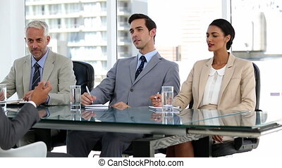 Job candidate talking to business people in a bright room