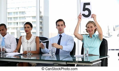 Business people showing scores - Smiling business people...