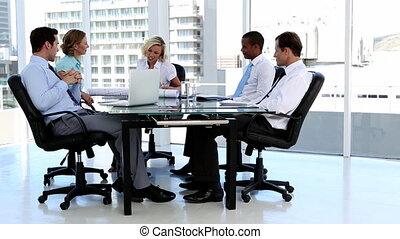 Business team talking around a desk in bright office